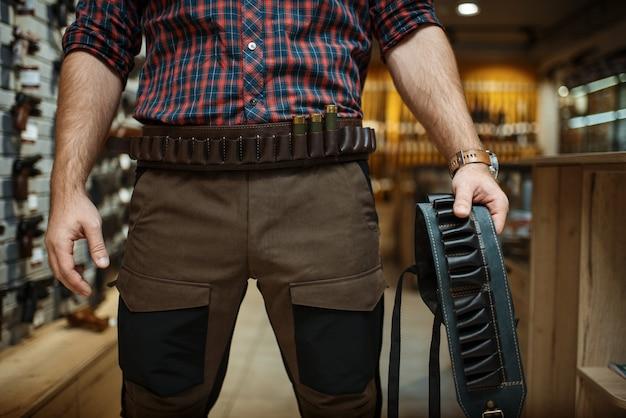 Un homme en uniforme de chasse tient une ceinture de munitions dans un magasin d'armes à feu.