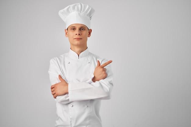 Un homme en uniforme de chef faisant des gestes avec une main travaillant dans un restaurant professionnel