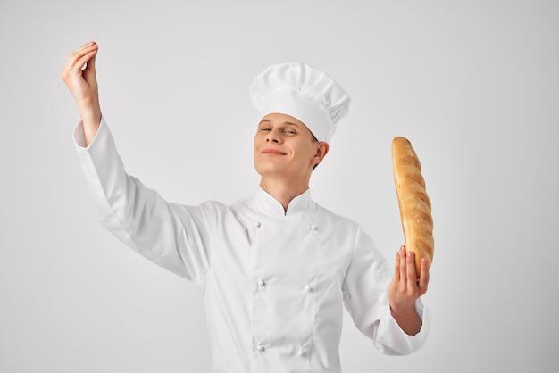 Un homme en uniforme de chef avec un pain dans ses mains fond clair de travail des aliments frais