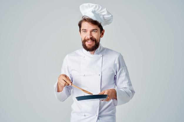 Un homme en uniforme de chef avec une poêle à frire professionnelle à la main