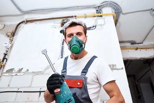 L'homme en uniforme de constructeur avec un marteau perforateur effectue des réparations dans la pièce.