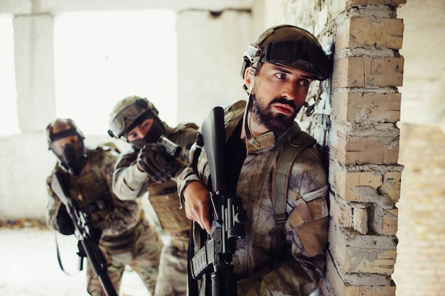 Homme en uniforme debout derrière le mur et en attente.