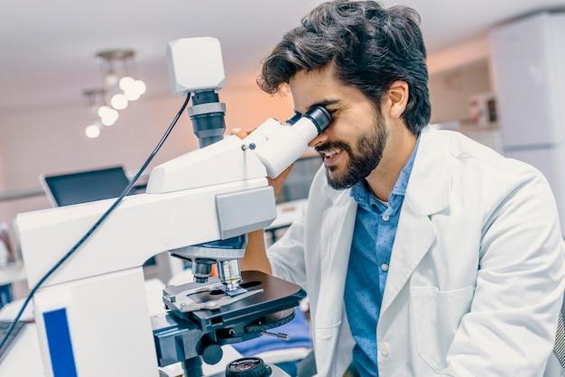 Homme en uniforme médical travaillant avec microscope faisant l'analyse au bureau du laboratoire