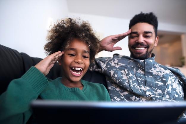 Homme en uniforme militaire et sa fille regardant l'écran de la tablette et saluant.