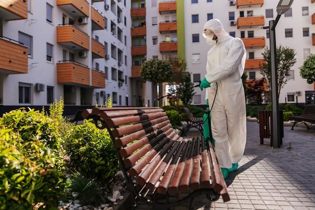 Homme en uniforme de protection stérile avec des gants en caoutchouc tenant un pulvérisateur avec un désinfectant et un banc de pulvérisation dans le parc afin d'éviter la propagation de la forme du virus corona.