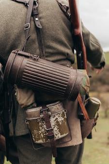 Un homme en uniforme de soldat avec une fiole et un tube lors de la reconstruction des hostilités. photo de haute qualité