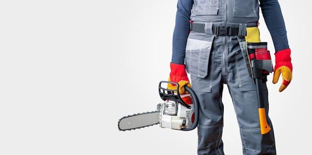 Homme en uniforme tenant une tronçonneuse sur une surface grise avec espace de copie. bannière. .construction, entrepreneur, réparation, bûcheron.