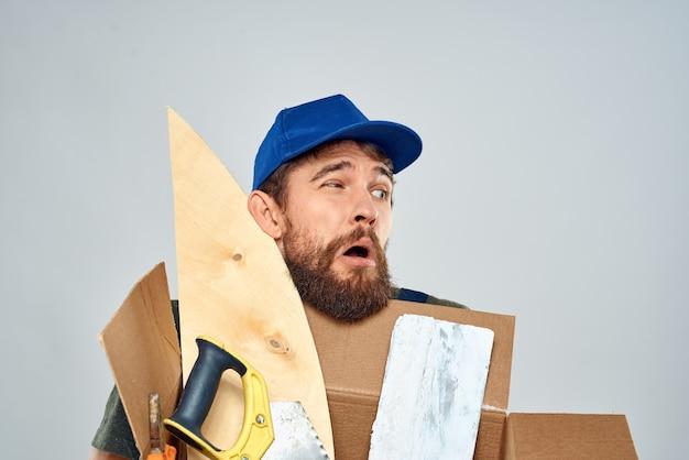 Homme en uniforme de travail avec boîte en mains outils lumière de style de vie.