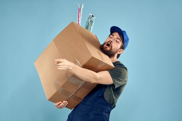 Un homme en uniforme de travail avec des boîtes dans les mains d'un espace bleu de service de livraison de chariot.
