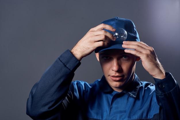 Homme en uniforme de travail lampe électricien professionnel outils