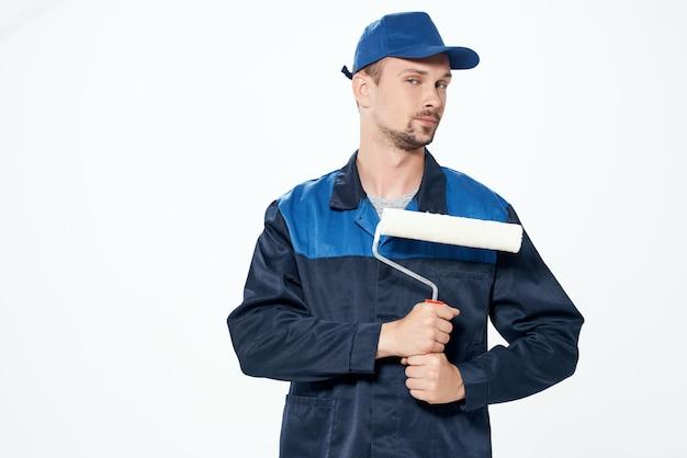 L'homme en uniforme de travail de réparation de rouleaux de peinture