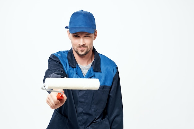 Un homme en uniforme de travail un rouleau pour peindre les murs dans ses mains la réparation de décoration