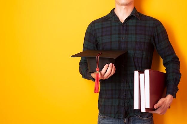 Homme d'université est heureux avec l'obtention du diplôme sur fond jaune