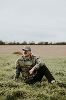 L'homme urbain dans une casquette de refroidissement sur le terrain d'herbe