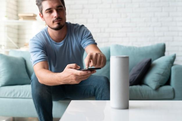 Homme utilisant un assistant numérique de haut-parleur