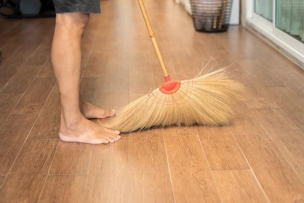 Un homme utilisant un balai de nettoyage à la maison, le nettoyage du sol, de l'équipement naturel d'occasion