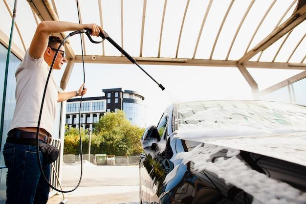 Homme utilisant un bâton pour pulvériser de l'eau sur la voiture