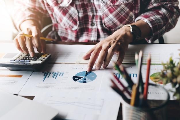 Homme utilisant une calculatrice tout en travaillant pour des documents financiers