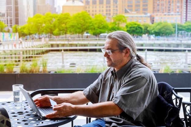 Homme utilisant une carte de crédit et un ordinateur portable, achats en ligne en plein air