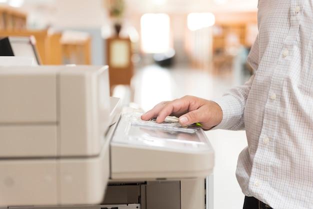 Un homme utilisant un copieur dans le bureau.