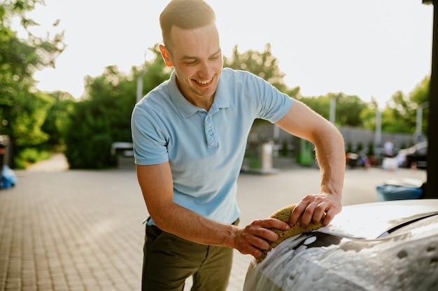 Homme utilisant une éponge avec de la mousse, lave-auto à la main