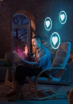 Homme utilisant un gadget et recevant des notifications au néon à la maison la nuit