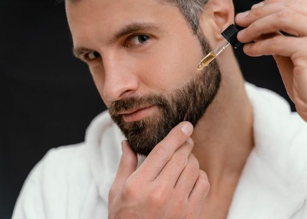 Homme utilisant des huiles naturelles pour son visage