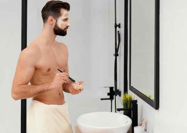 Homme utilisant des ingrédients naturels pour un masque facial