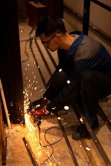 Homme utilisant une meuleuse d'angle avec des étincelles