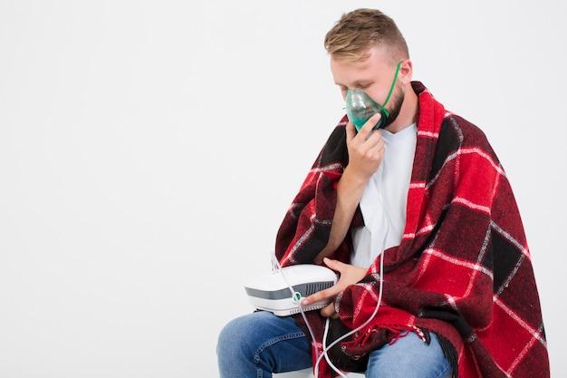 Homme utilisant un nébuliseur pour l'asthme