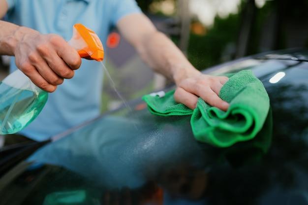 Homme utilisant un nettoyant pour vitres et un chiffon, lavage automatique à la main