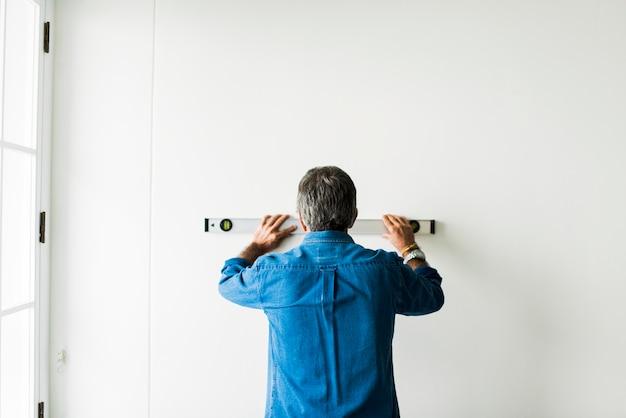 Homme utilisant un niveau à bulle sur un mur
