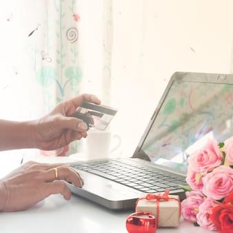 Homme utilisant un ordinateur et une carte de crédit avec des cadeaux et des roses sur une table