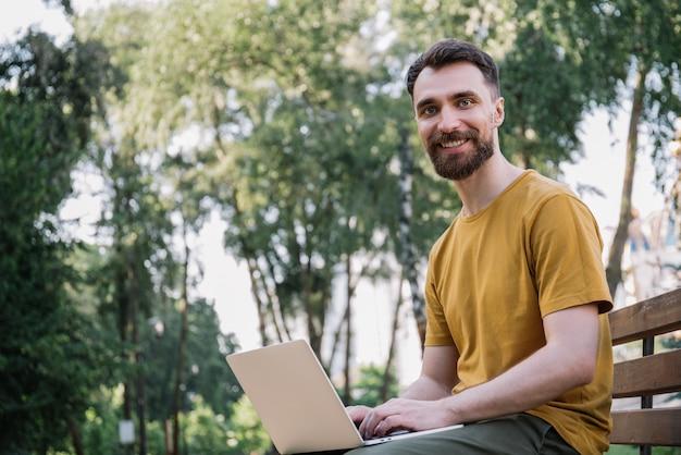 Homme utilisant un ordinateur portable, assis sur un banc. freelance travaillant dans le parc