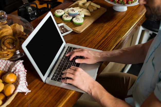 Homme utilisant un ordinateur portable au comptoir dans un café