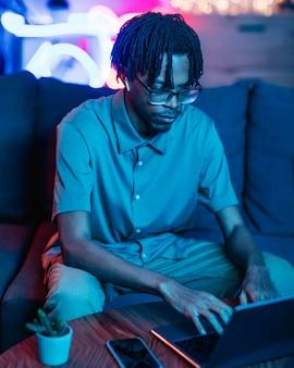 Homme utilisant un ordinateur portable sur le canapé à la maison