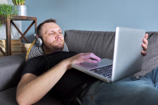 Homme utilisant un ordinateur portable à la maison, homme se relaxant allongé sur un canapé regardant un écran d'ordinateur portable, repos et loisirs, travail d'entreprise et étude de l'éducation