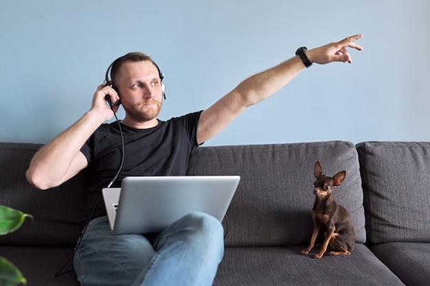 Homme utilisant un ordinateur portable à la maison, homme se relaxant assis sur un canapé avec des écouteurs écoutant et profitant de la musique, du repos et des loisirs, arrière-plan à la maison
