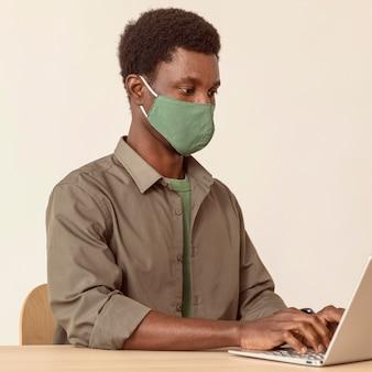 Homme utilisant un ordinateur portable et portant un masque