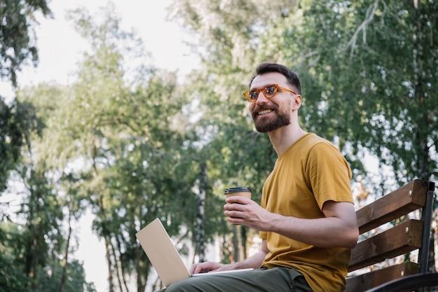 Homme utilisant un ordinateur portable, tenant une tasse de café, travaillant dans le parc assis sur un banc