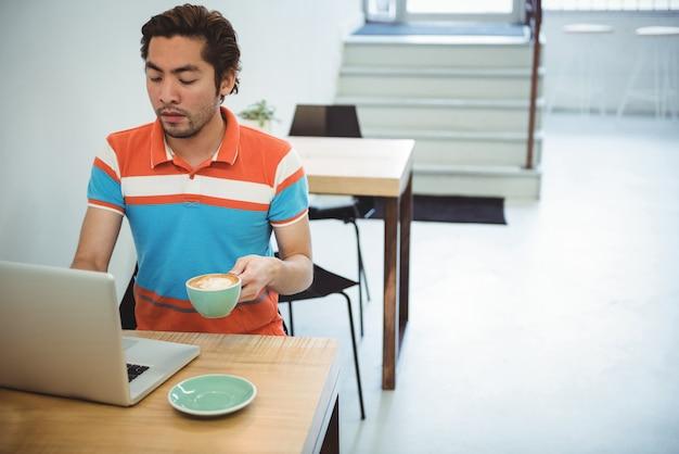 Homme utilisant un ordinateur portable tout en ayant une tasse de café
