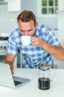 Homme utilisant un ordinateur portable tout en buvant du café dans la cuisine