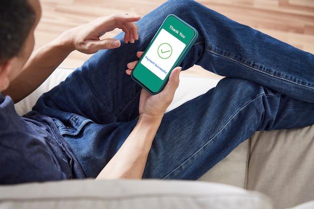 Un homme utilisant le paiement en ligne de smartphone à la maison