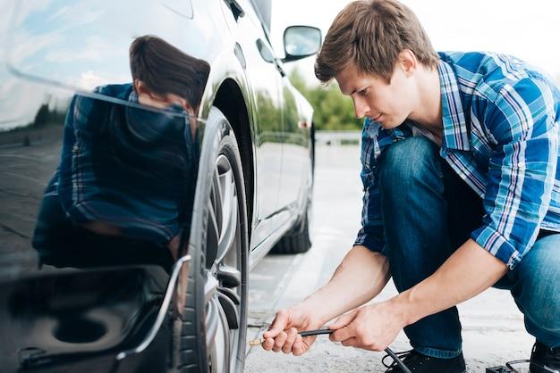 Homme utilisant une pompe à air sur pneu