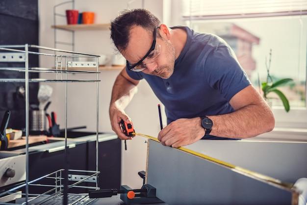 Homme utilisant un ruban à mesurer