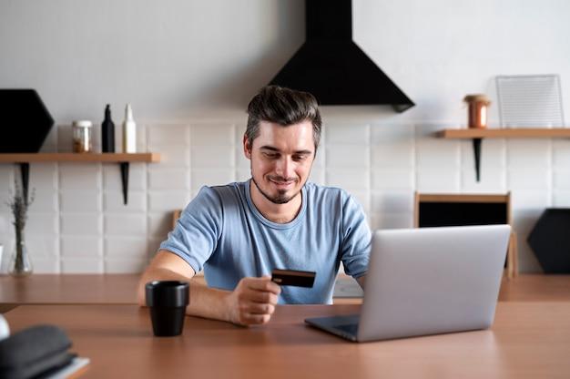 Homme utilisant sa carte de crédit pour jouer en ligne pour une commande