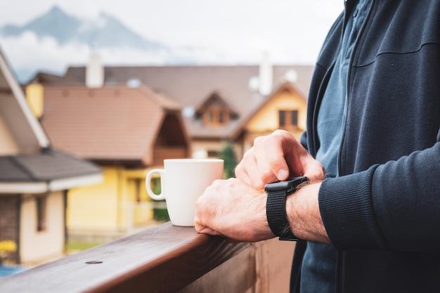 Homme utilisant sa montre intelligente sur le balcon et buvant du café avec une vue imprenable sur les montagnes