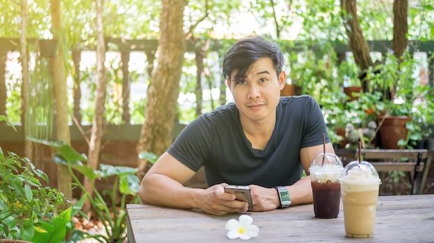 Homme utilisant un smartphone dans un café.
