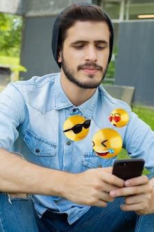 Homme utilisant un smartphone envoyant des emojis