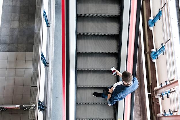 Homme utilisant un smartphone sur l'escalator